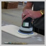 Joiner sanding top with orbital sander, prior to staining